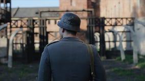 Eine hintere nahe Ansicht eines deutschen Soldaten, der langsam zum Tor einer unscharfen Konzentrationslagerrekonstruktion geht l stock video footage