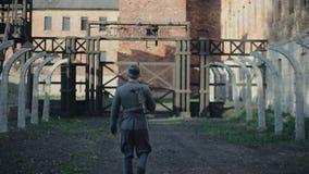 Eine hintere nahe Ansicht eines deutschen Soldaten, der langsam zum Tor einer unscharfen Konzentrationslagerrekonstruktion geht l stock footage