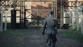 Eine hintere nahe Ansicht eines deutschen Soldaten, der langsam zum Tor einer unscharfen Konzentrationslagerrekonstruktion geht l stock video
