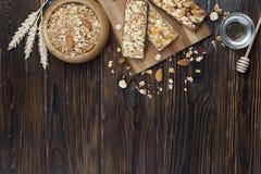Eine Hintermischungsschüssel Trockenfrüchte, Rosinen, Moosbeere mit Mandeln, Rosinen, Samen, Acajoubaum, Haselnussnüsse mit Honig Lizenzfreie Stockfotos