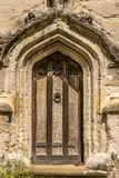 Eine hohe alte Holztür mit einem Klopfer mitten in ihm stockbild