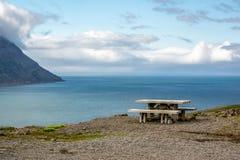 Eine Holzbank auf einem Hügel mit schöner Aussicht in Island Stockbild