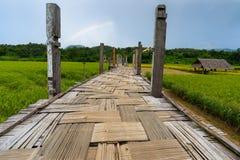 Eine Holzbrücke und eine Hütte auf dem grünen Gebiet Stockfotos