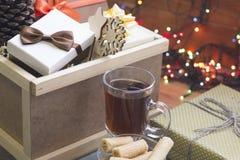 Eine Holzkiste, Geschenke und eine Tasse Tee Lizenzfreie Stockfotos