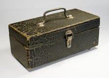 Eine Holzkiste mit einem Metallgriff und einer Klinke auf einem hellen Hintergrund Der Kasten wird mit Farbe gemalt, die geknackt Lizenzfreie Stockfotografie
