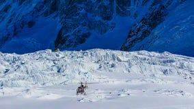 Eine Hubschrauberfliege über Bergen in den Alpen lizenzfreie stockfotos