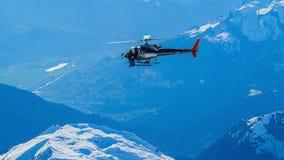 Eine Hubschrauberfliege über Bergen in den Alpen lizenzfreies stockfoto