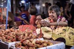 Eine identifizierte Frau verkauft Kalebassen stockbild