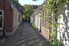 Eine idyllische, schmale Straße in Garnwerd, die Niederlande Lizenzfreie Stockfotografie