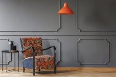 Eine industrielle Seitentabelle und ein boho Lehnsessel in einem eleganten, grauen Wohnzimmerinnenraum mit Formteil und Platz für stockfoto
