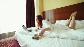 Eine Ingwerfrau, die auf dem Bett liegt und mit einem Laptop - Getränktee arbeitet stock video