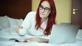 Eine Ingwerfrau im Bademantel, der auf dem Bett und dem trinkenden Tee liegt - arbeitend mit einem Laptop - freiberuflich tätiger stock video footage