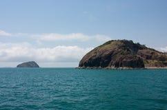 Eine Insel im Hintergrund und ein Zutageliegen an der Rosslyn-Bucht nahe Yeppoon im Steinbockbereich in Mittel-Queensland, Austra lizenzfreies stockbild
