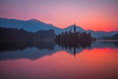 Eine Insel mit Kirche in ausgeblutetem See, Slowenien bei Sonnenaufgang Stockfotografie