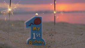 Eine jährige Babygeburtstagskerze auf dem Strand stock video footage