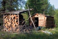 Eine Jagdkabine und ein Stapel des Brennholzes in der Nähe Lizenzfreie Stockfotografie