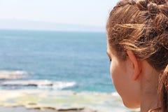 Eine Jugendliche betrachtet das Meer unten Stockfotos