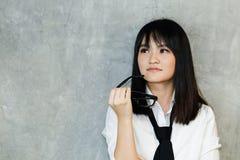 Eine Jugendliche, die auf einer Wand sich lehnt Lizenzfreie Stockfotografie