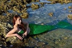 Eine Jugendliche in einem grünen Meerjungfraukostüm liegt im Wasser unter den Steinen lizenzfreies stockfoto