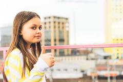 Eine Jugendliche in einer gelben Strickjacke steht gegen das Stadtbild stockfotografie