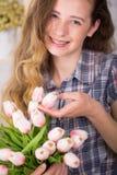 Eine Jugendliche lächelt mit Birken Aufstellung gegen einen Backsteinmauerhintergrund mit einem Blumenstrauß von Tulpen Stockbilder