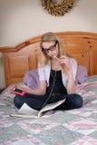Eine Jugendliche liest beim Hören Musik. Stockfotos