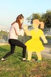 Eine Jugendliche macht Spaß mit einer Statue Stockbild