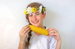 Eine Jugendliche mit einem Blumenstrauß auf ihrem Kopf isst Mais Stockfoto