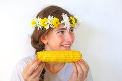 Eine Jugendliche mit einem Blumenstrauß auf ihrem Kopf isst Mais Stockbilder