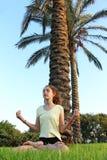 Eine Jugendliche sitzt auf einem Rasen und meditiert lizenzfreies stockfoto