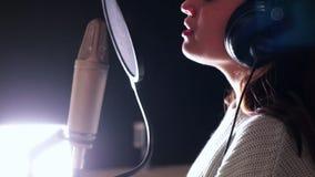 Eine junge attraktive Frau, die im Tonstudio singt stock footage