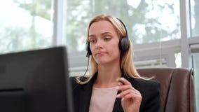 Eine junge attraktive Frau, die eine schwarze Jacke in einer schwarzen Jacke trägt, sitzt an ihrem Schreibtisch in einem Exekutiv stock video footage