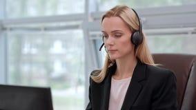 Eine junge attraktive Frau, die eine schwarze Jacke in einer schwarzen Jacke trägt, sitzt an ihrem Schreibtisch in einem Exekutiv stock footage