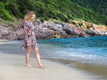 Eine junge blonde behaarte Frau, die entlang den Strand geht Stockbilder