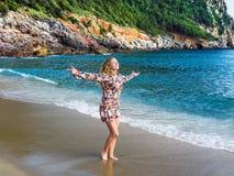 Eine junge blonde behaarte Frau, die entlang den Strand geht Stockfotos
