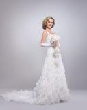 Eine junge blonde Braut, die in einem langen weißen Kleid aufwirft Lizenzfreies Stockbild