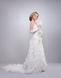 Eine junge blonde Braut, die in einem langen weißen Kleid aufwirft Lizenzfreie Stockfotos
