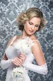 Eine junge blonde Braut, die in einem langen weißen Kleid aufwirft Lizenzfreie Stockfotografie