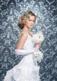 Eine junge blonde Braut, die in einem langen weißen Kleid aufwirft Stockbilder