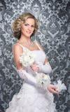 Eine junge blonde Braut, die in einem langen weißen Kleid aufwirft Stockfoto