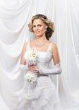Eine junge blonde Braut, die in einem weißen Kleid aufwirft Stockfotografie