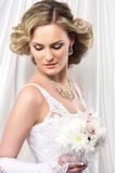 Eine junge blonde Braut, die in einem weißen Kleid aufwirft Lizenzfreie Stockbilder