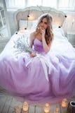 Eine junge blonde Braut in einem ausgezeichneten purpurroten Kleid, das auf dem Bett sitzt In den Raumkerzen Mädchengriffe in den Stockfoto