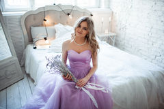 Eine junge blonde Braut in einem ausgezeichneten purpurroten Kleid, das auf dem Bett sitzt In den Raumkerzen Mädchengriffe in den Lizenzfreie Stockfotos