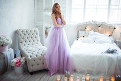 Eine junge blonde Braut in einem ausgezeichneten purpurroten Kleid ist im Schlafzimmer In den Raumkerzen und in den Blumensträuße Stockbilder