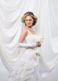 Eine junge blonde Braut in einem weißen Kleid Lizenzfreie Stockbilder