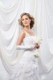 Eine junge blonde Braut in einem weißen Kleid Lizenzfreie Stockfotos