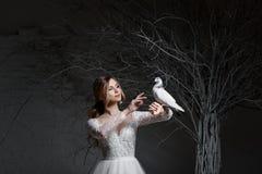 Eine junge blonde Braut im weißen Hochzeitskleid auf einem Hintergrund von weißen Wänden und weißem Baum im Hintergrund hält a Stockfotografie
