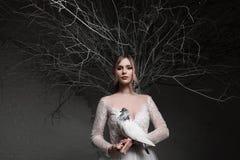 Eine junge blonde Braut im weißen Hochzeitskleid auf einem Hintergrund von weißen Wänden und weißem Baum im Hintergrund hält a Stockbilder