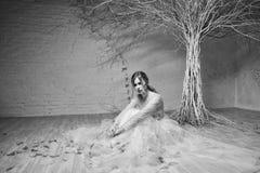 Eine junge blonde Braut im weißen Hochzeitskleid auf einem Hintergrund von weißen Wänden und weißer Baum im Hintergrund Stockfotografie